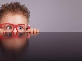 Fundación Alain Afflelou. Niño asomado con gafas rojas
