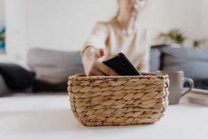 Minimalismo digital. Mujer deja el teléfono en una cesta