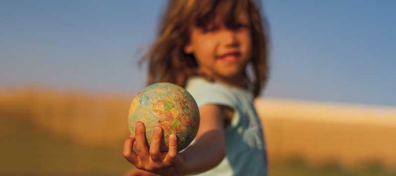 Niña sostiene bola del mundo. Políticas familiares